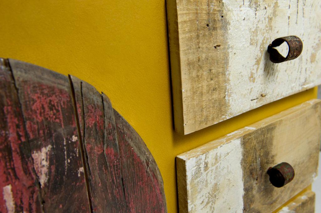 Credenza lunga con struttura in MDF ricoperto di resina color ocra per legno. I frontali dei cassetti, le porte e la botola sono in legno vintage rigenerato.