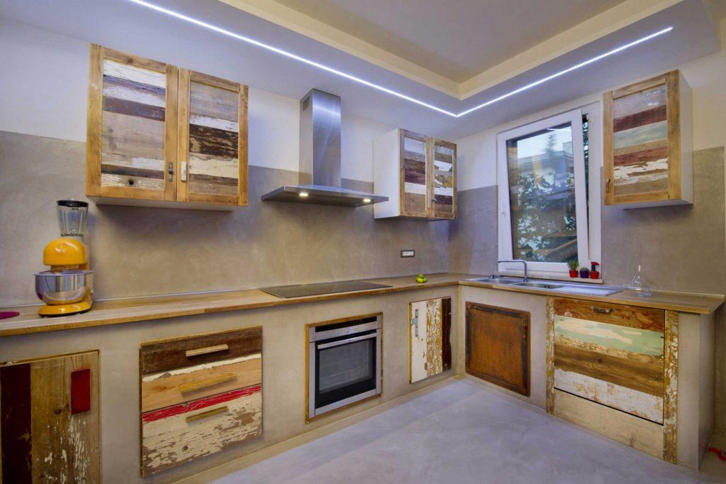 Cucina in resina stile industriale e sportelli e cassetti in legno di recupero colorato