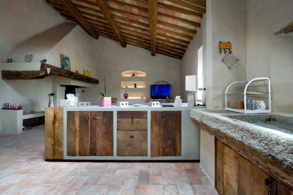 Cucina su misura in villa toscana nel Chianti con lavabo in pietra e legno di recupero