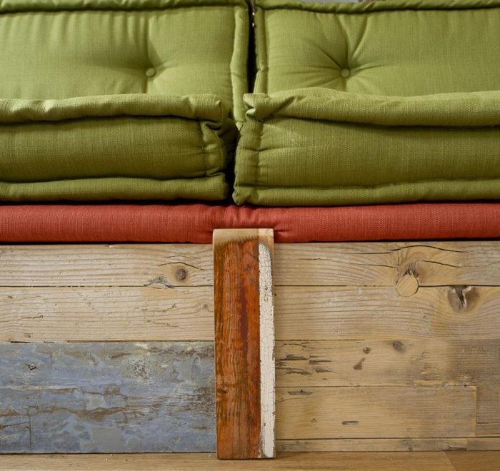 Soggiorno con divano in legno e stoffa vintage artigianale. Collaborazione con Abiuno