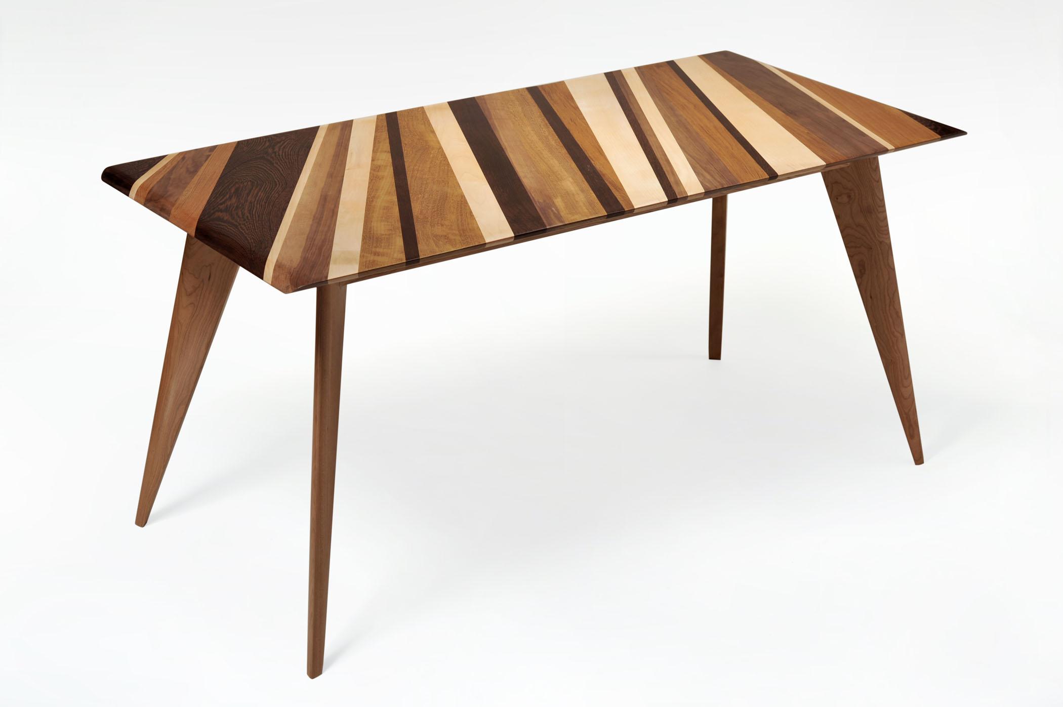 Tavolo in legno massello. Piano con diversi legni: noce, acero, wengè, teak.