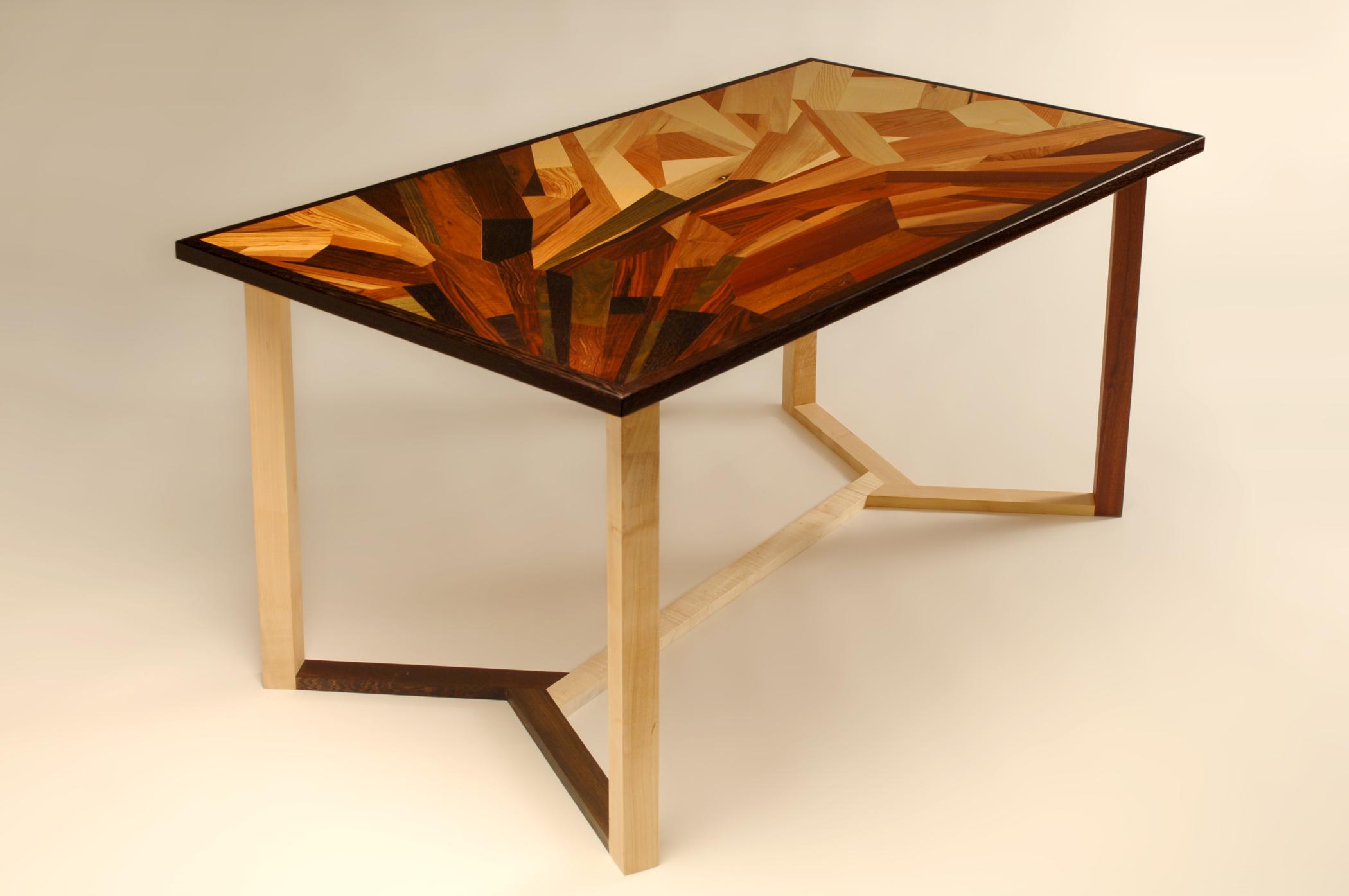 Tavolo di design con piano intarsiato e struttura in legno massello monocromatico