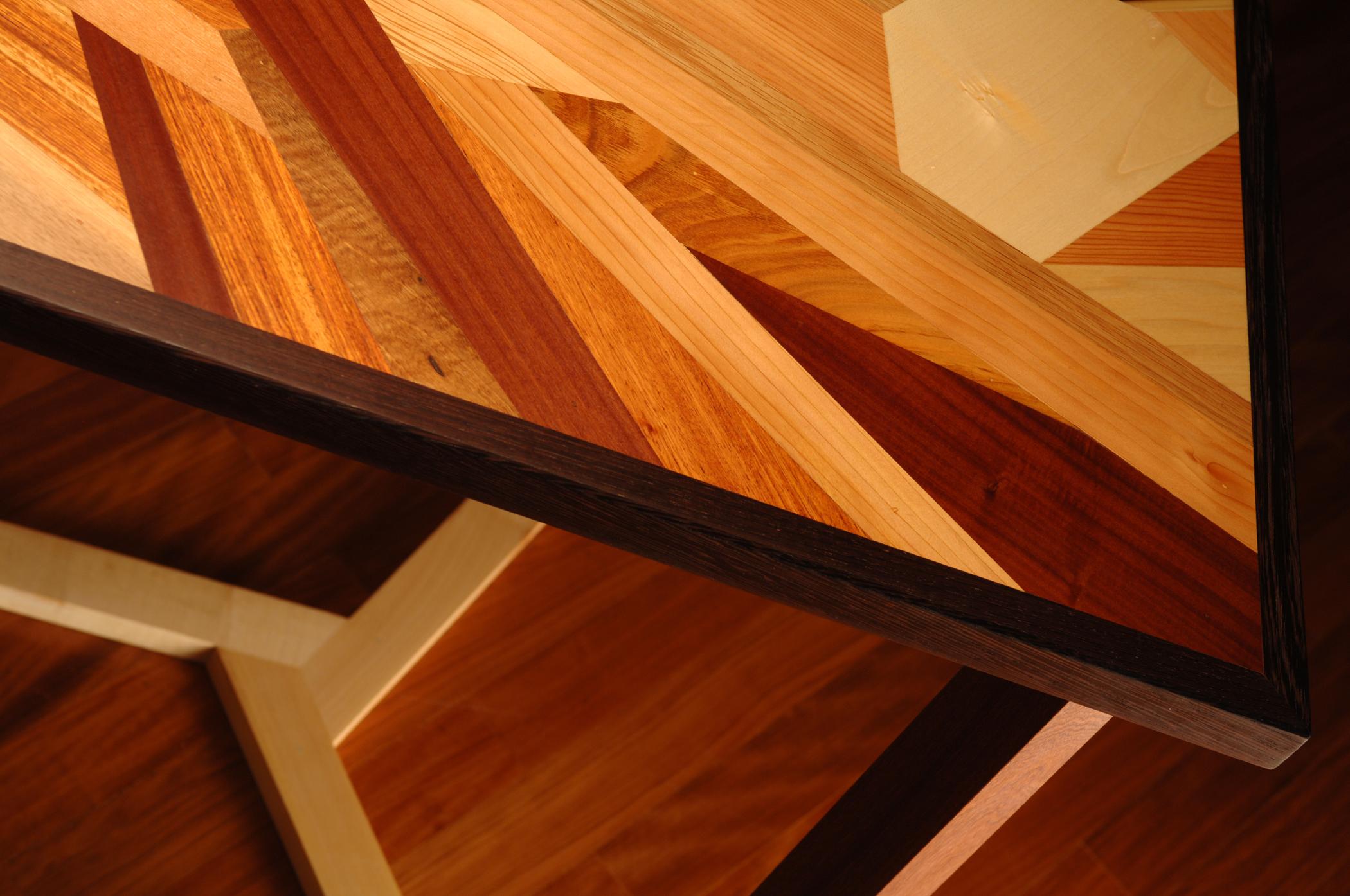 Tavolo intarsiato contemporaneo con frammenti di legno massello di diversi colori.