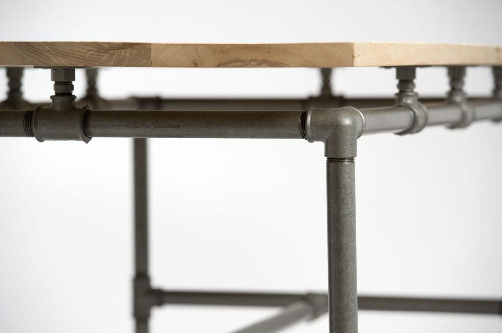 Tavolo con piano fatto con listelli da costruzione di legno restaurato e gambe costruite con tubi idraulici