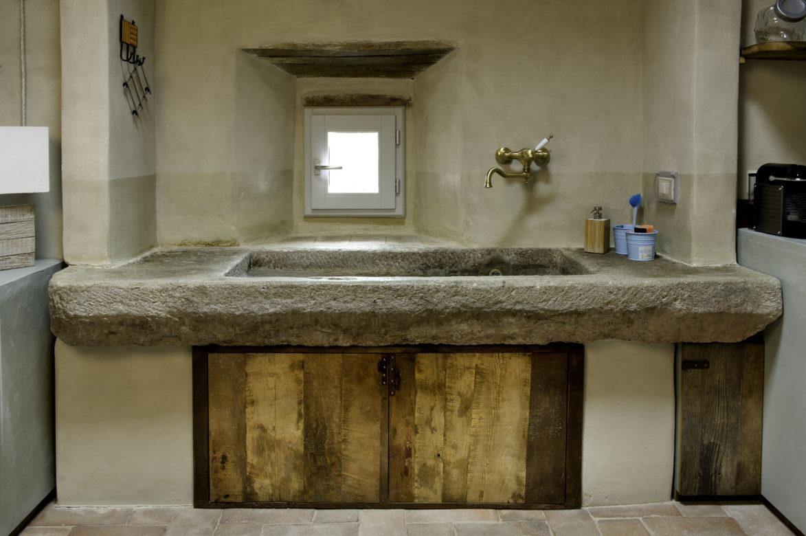 Lavabo in pietra in una cucina con legno vintage