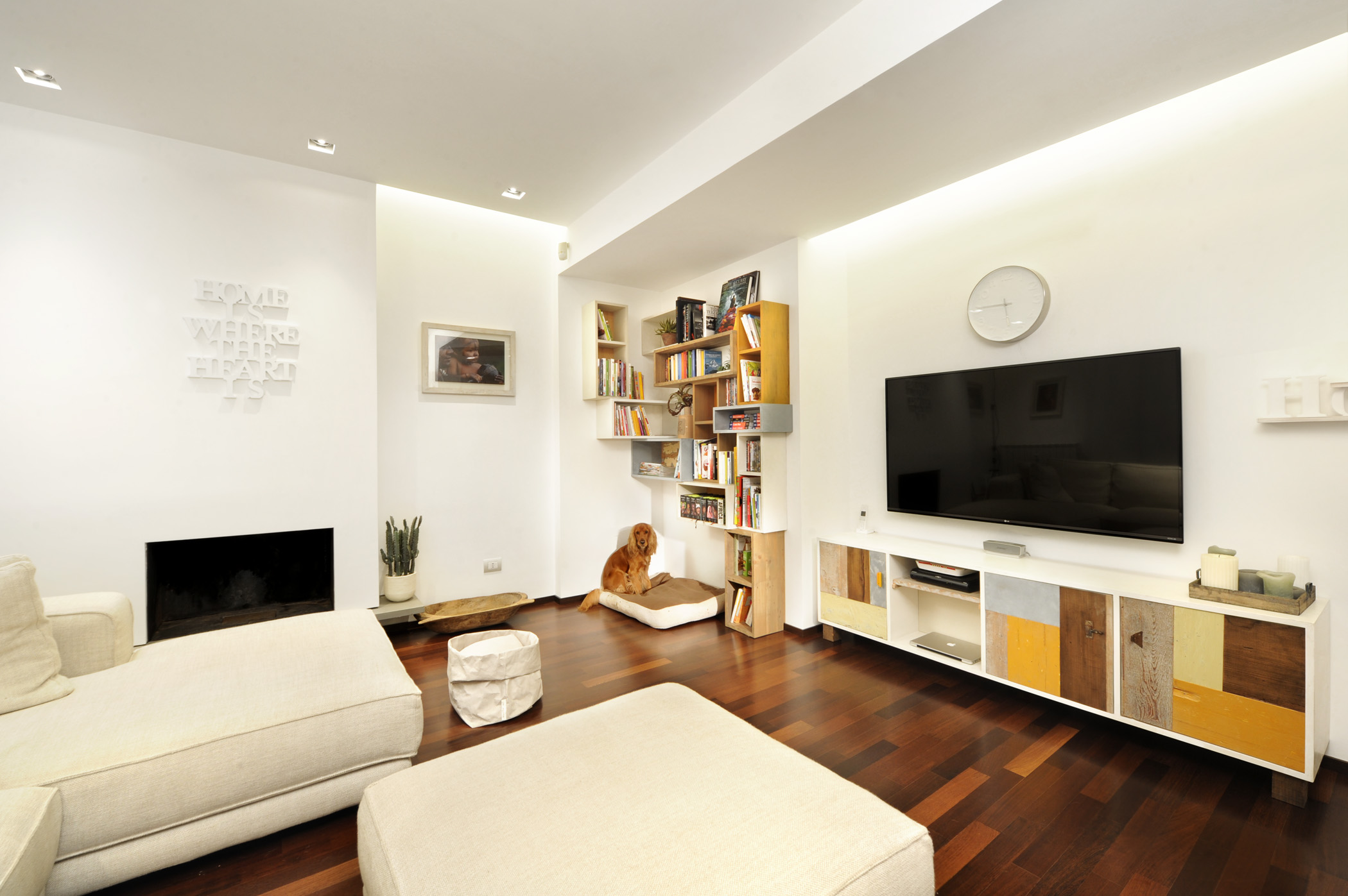 Soggiorno con credenza su misura e parete attrezzata con pensili e moduli in legno colorato
