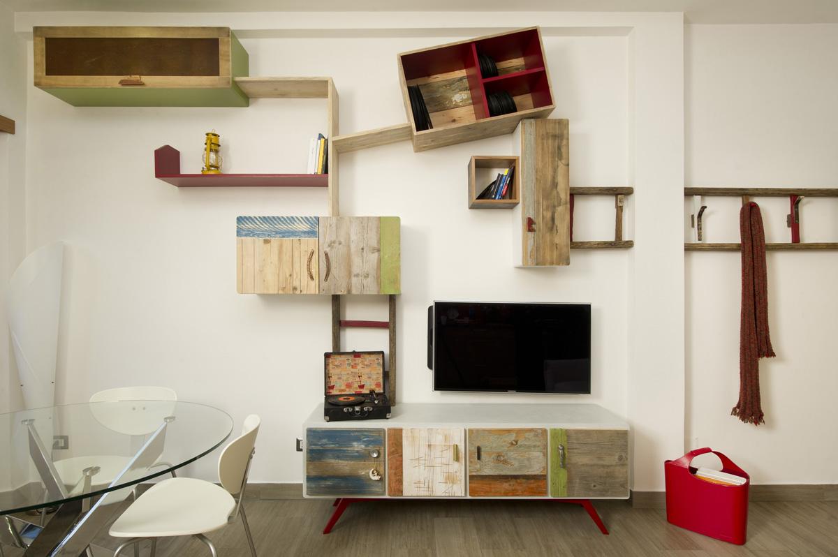 Parete attrezzata moderna Ginevra in legno di recupero, con vecchi oggetti tra cui una scala in legno.