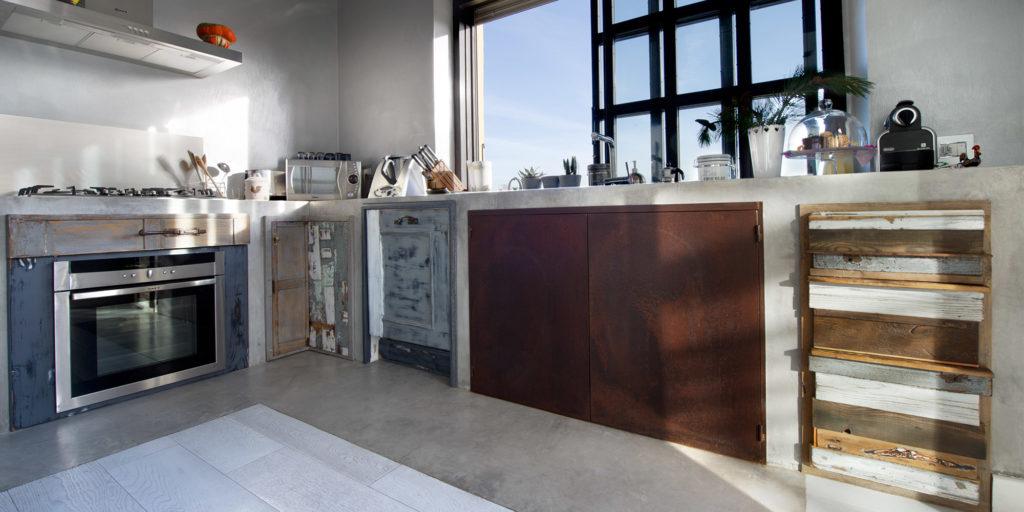 cucina in finta muratura e ante in legno massello stile industriale rivestimento in resina e ferro ossidato