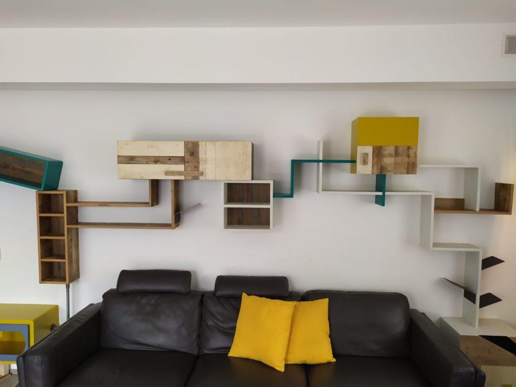 parete attrezzata colorata moderna con tubi industriali e legno di recupero